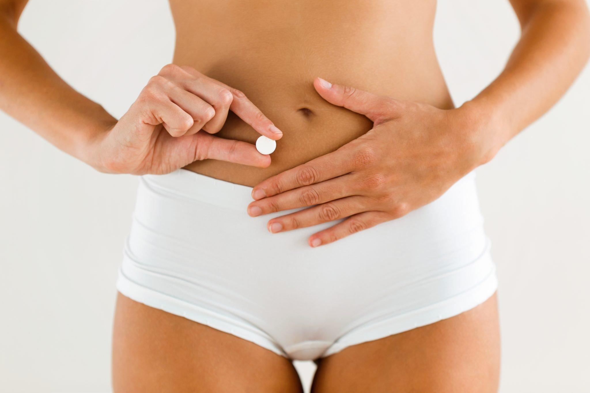 szczupły kobiecy brzuch i dłoń trzymająca probiotyki