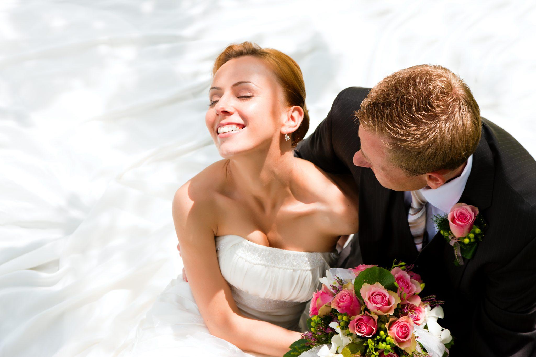 Para młoda, roześmiana, eksponuje ślubną wiązankę - pod strojami ślubnymi mają antybąkowy zestaw ślubny dla niej i dla niego i dzięki temu ich ślub pachnie wyłącznie kwiatami