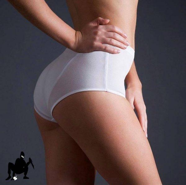 damskie klasyczne białe majtki antybąkowe na pupie szczupłej modelki, widziane z boku