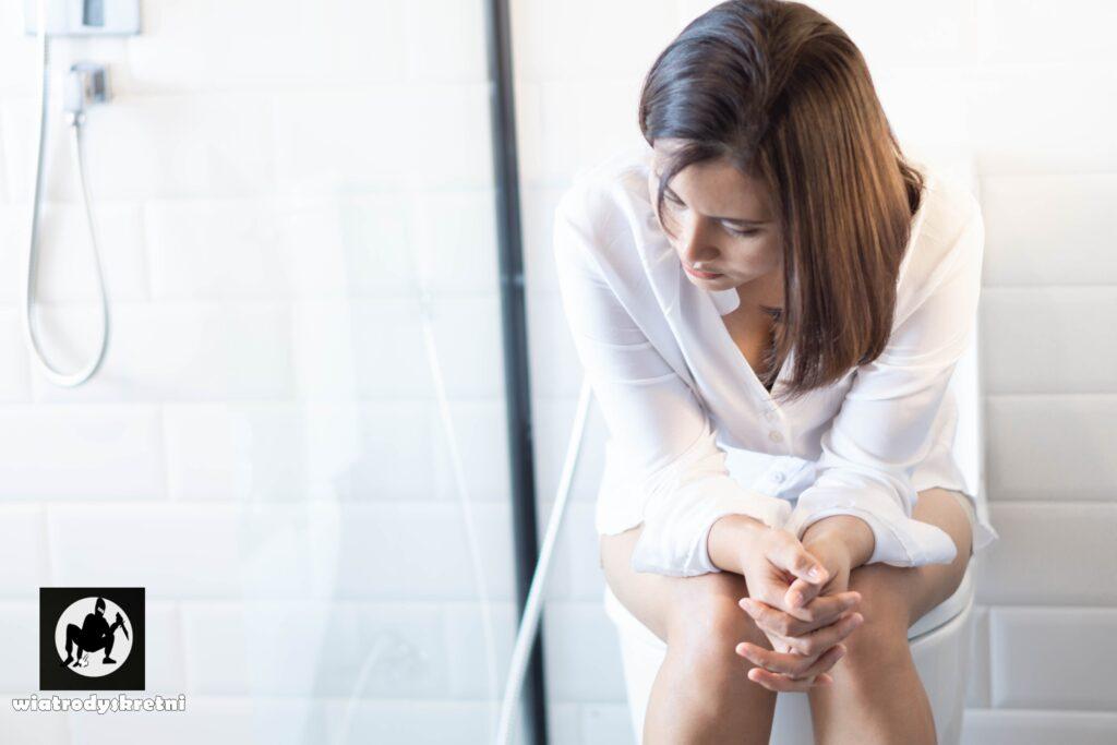 niekorzystne dla zdrowia nawyki - wstrzymywanie kału - dziewczyna w białej bluzce siedzi na toalecie w jasnej łazience