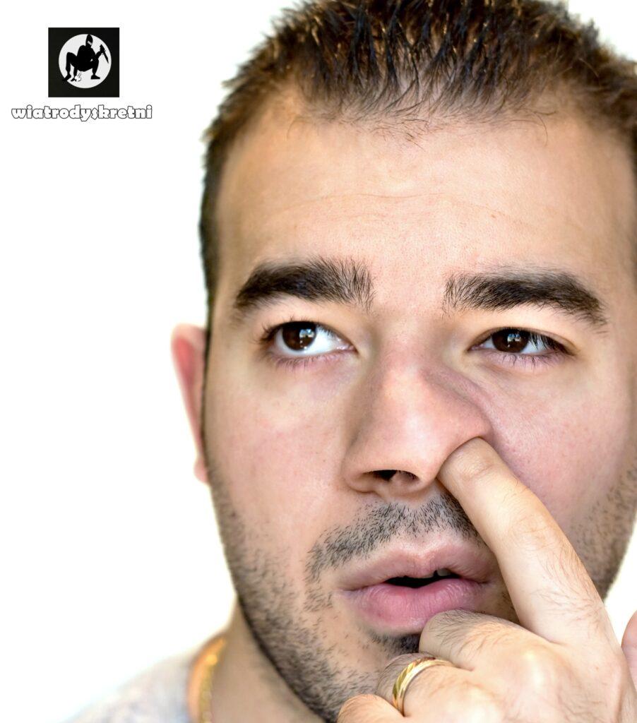 szkodliwe dla zdrowia nawyki - zbliżenie na twarz mężczyzny młodego ciemnookiego przyjemnie wyglądającego który dłubie w nosie